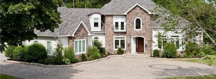 paved driveway and stone exterior home