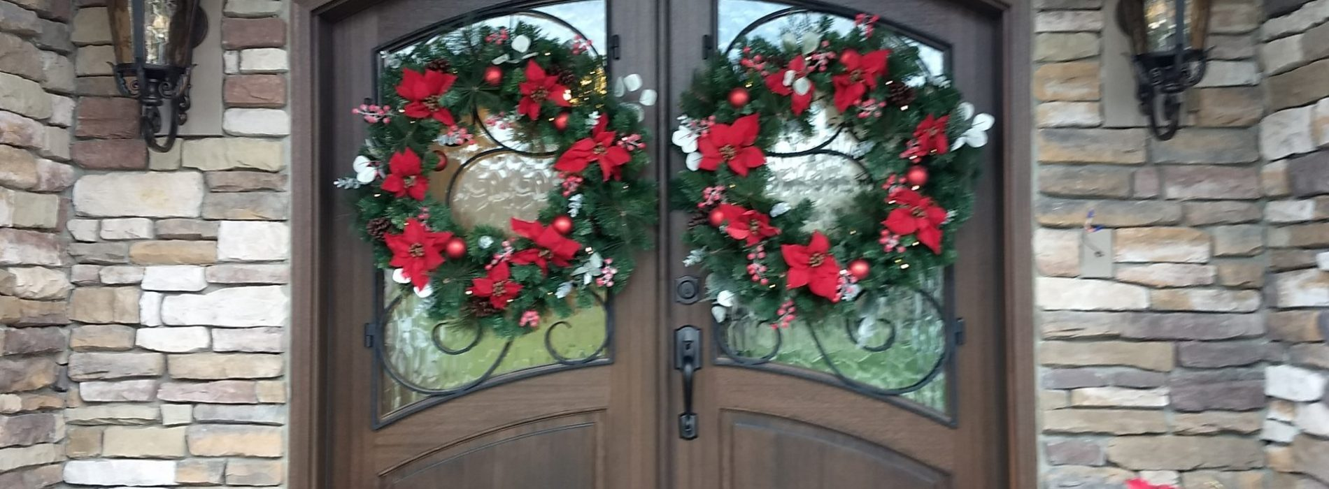 grand entrance doorway with holiday flowers and wreaths
