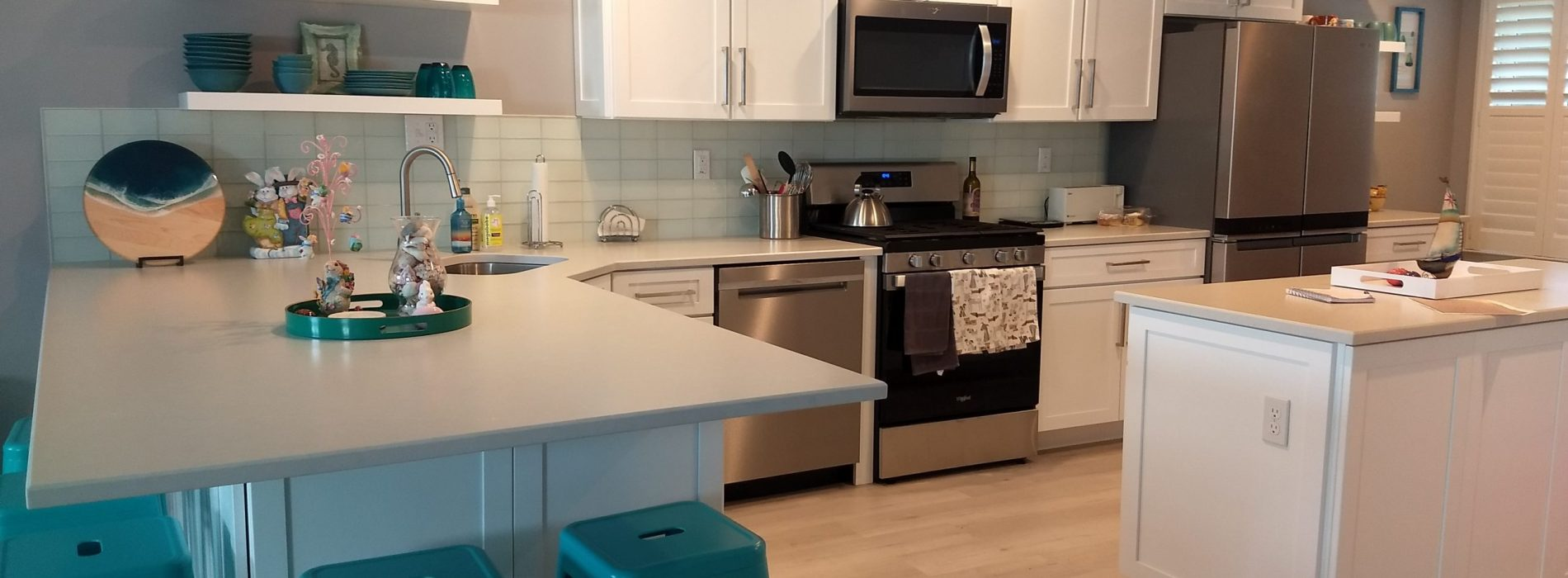 white with blue accent kitchen renovaiton with a bfast bar and island