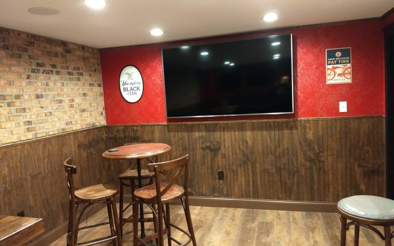 table seating and tv in basement bar and pub